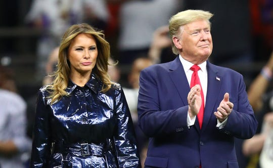 President Donald J. Trump and First Lady Melania Trump walk onto the field before the College Football Playoff national championship game at Mercedes-Benz Superdome.