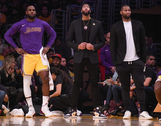 The Lakers' LeBron James, left, Anthony Davis, center, and DeMarcus Cousins, right, watch the action during Monday's game against the Cleveland Cavaliers.