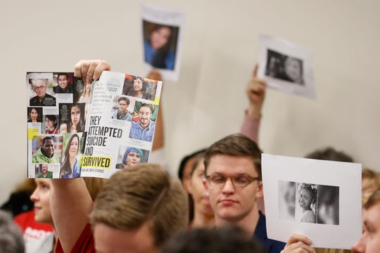 Supporters of gun control hold up photos of gun violence victims during a meeting of the Senate Judiciary committee at the Capitol in Richmond, Va., on Jan. 13.