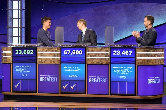James Holzhauer, left, shakes Ken Jennings' hand after Jennings won his second match Thursday in the 'Jeopardy!: The Greatest of All Time' tournament. Brad Rutter, right watches.