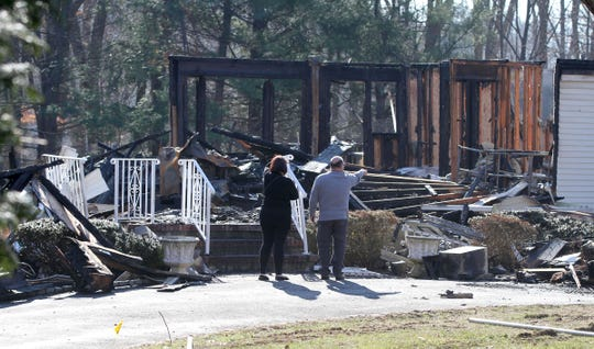 People walk outside 42 Raven Road in Colts Neck Wednesday, January 15, 2020.  The Monmouth County Prosecutor's office has reported that Joseph Apisa was trapped inside his first floor bedroom and killed in a Tuesday morning fire here.