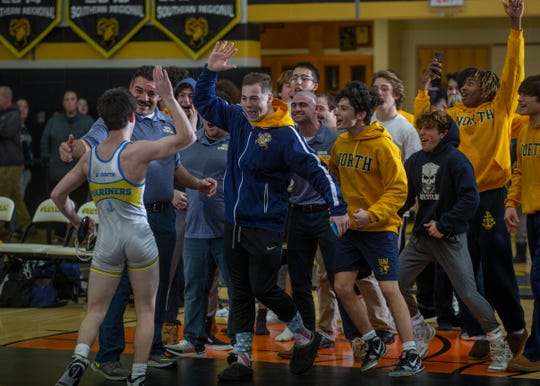Toms River North's Jake Rosenthal is congratulated by his teammates and Mariners' head coach Bill Wilbert (left) after his 8-6 win over Southern's Nick Bennet in the final bout at 126 pounds gave Toms River North a come-from-behind 28-26 win Tuesday night.