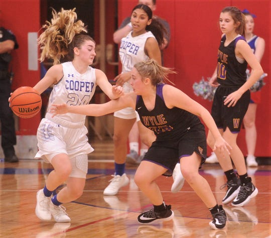 Wylie's Makinlee Bacon pressures Cooper's Meri Tetaj, right, in the second half. The Lady Coogs beat Wylie 69-40 in the District 4-5A game Tuesday, Jan. 14, 2020, at Cougar Gym.