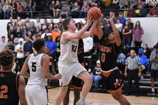 Abilene High's Nathan Watts (32) gets fouled by a Haltom City Haltom defender going to the basket at Eagle Gym on Tuesday. Watts finished with 10 points in the 52-39 win.