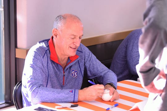Radio broadcaster Eric Nadel signs a baseball during the Texas Rangers Winter Caravan stop at the Whataburger on Danville in Abilene on Tuesday, Jan. 14, 2020.