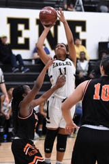 Abilene High's Destiny Potts (11) fights through contact for a shot against Haltom City Haltom at Eagle Gym on Tuesday. The Lady Eagles won 48-44 for their first district win.