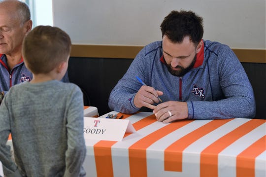 Pitcher Nick Goody signs a ball for a young fan during the Texas Rangers Winter Caravan stop at the Whataburger on Danville in Abilene on Tuesday, Jan. 14, 2020.