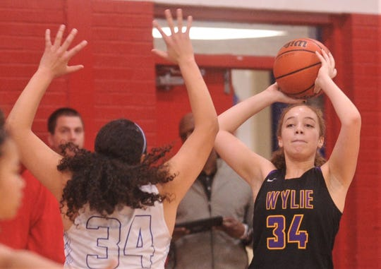 Wylie's Mason Lambert (34) looks to the pass the ball while Cooper's Kaleigha Kemp defends. Cooper beat the Lady Bulldogs 69-40 in the District 4-5A game Tuesday, Jan. 14, 2020, at Cougar Gym.
