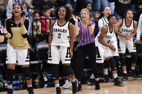 Abilene High coach Terri Aston, middle, Destiny Potts, far left, and Syncere Reed (2) celebrate the game-winning basket against Haltom City Haltom at Eagle Gym on Tuesday. The Lady Eagles scored the final six points to win 48-44.