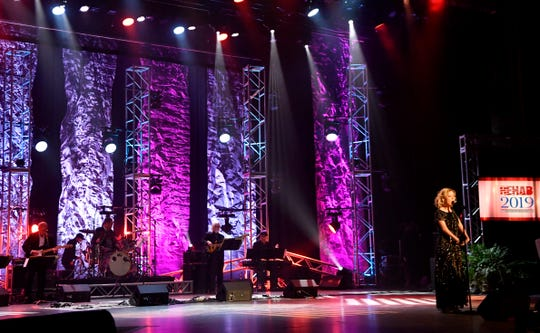 The Rehab house band backs singer Rion Paige during her performance at the 2019 telethon. The musicians are hard to see but vital to the performances of guest artists such as Paige. Bassist Dave Kewon is barely visible behind Paige and to the left.
