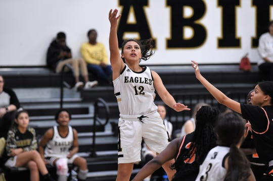Abilene High's Justine Martinez (12) follows through on a layup against Haltom City Haltom on Tuesday. Martinez got a steal and scored to tie the game late and finished with her seventh point on a free throw to put away the 48-44 win.