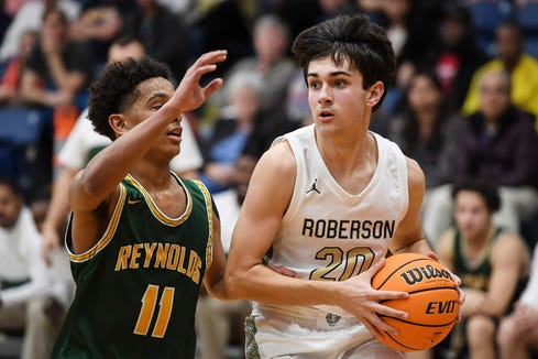 Roberson's Spencer Cable (20) drives against Reynolds' Malaki Carter (11) during the Rams'  47-45 victory January 14, 2020.