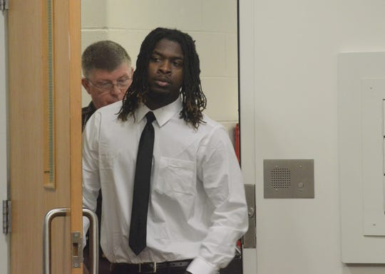 Khanas Ware, 22, enters the courtroom for this murder trial.