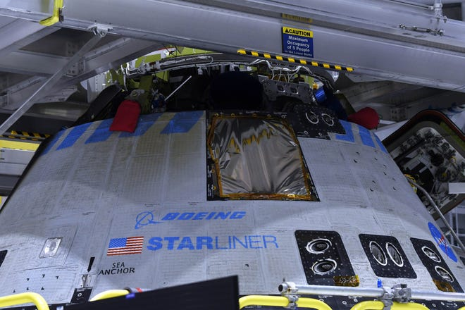 Members of the news media get a closer look at Boeing's Starliner capsule.