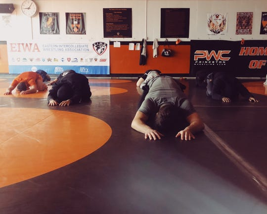 Princeton University wrestlers perform a yoga pose during a workout. The Tigers have embraced the practice to help recover from the grind of the season.