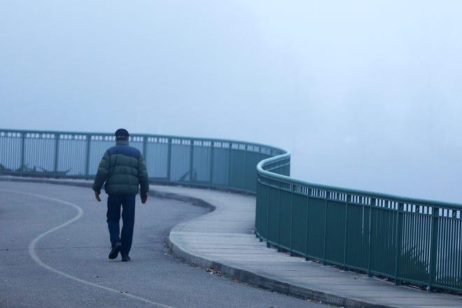 A man walks as fog surrounds Winton Woods Park Tuesday, January 14, 2020.