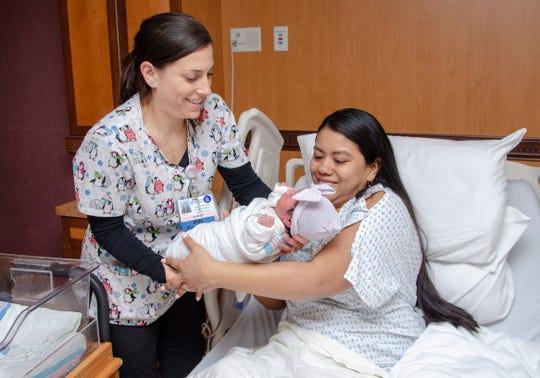 Nurse manager Ashley Zapolski, BSN, RNC-MNN (left), hands Ariana to her mother, Maria Noscue-Prado, at Saint Peter's University Hospital.