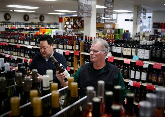 Ben Jung, left, and Mark Davison of Ingersoll Wine and Spirits in Des Moines look over bottles of French imported wine on Wednesday, Jan. 15, 2020.
