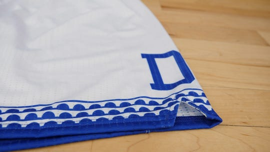 "The uniform shorts for Drake University's ""hometown team"" weekend of basketball games include the city of Des Moines' arched-bridge imagery from its flag on the hem, along with a traditional Drake block ""D."""