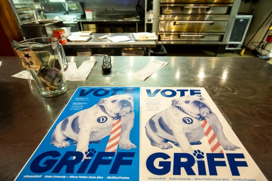 Signs with images of Griff, the living mascot at Drake University, are displayed at a front counter during a watch party for the CNN/Des Moines Register Democratic Presidential Debate, Tuesday, Jan. 14, 2020, at Papa Keno's Pizzeria in Des Moines, Iowa.