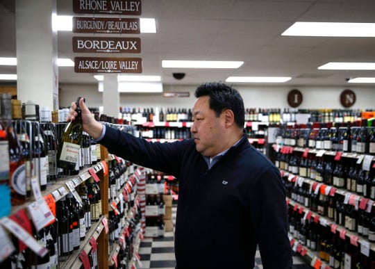 Ben Jung of Ingersoll Wine and Spirits in Des Moines places a bottle of French imported wine back on the shelf on Wednesday, Jan. 15, 2020.