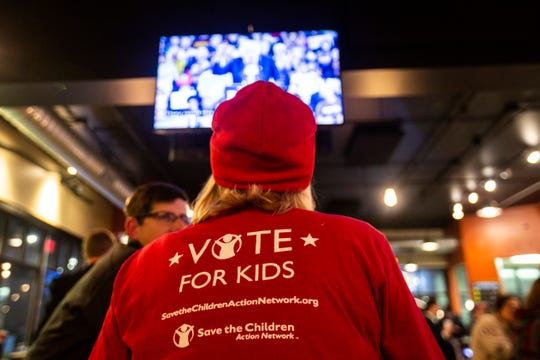 A member of Save the Children Action Network watches the CNN/Des Moines Register Democratic Presidential Debate, Tuesday, Jan. 14, 2020, at Papa Keno's Pizzeria in Des Moines, Iowa.