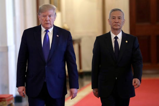 President Donald Trump walks before signing a trade agreement with Chinese Vice Premier Liu He, right, in the East Room of the White House, Wednesday, Jan. 15, 2020, in Washington. (AP Photo/Evan Vucci)
