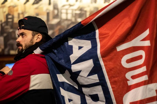Tully Baker, of New Hampshire, carries a flag in support of Democratic presidential candidate Andrew Yang during a watch party for the CNN/Des Moines Register Democratic Presidential Debate, Tuesday, Jan. 14, 2020, at Papa Keno's Pizzeria in Des Moines, Iowa.