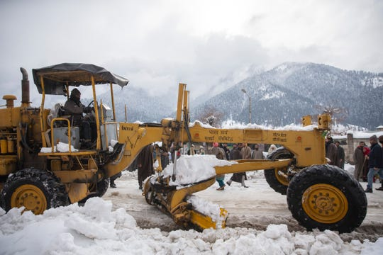 Snow clearing machine clears snow from a road in Kangan, north of Srinagar, Indian controlled Kashmir, Tuesday, Jan. 14, 2020.