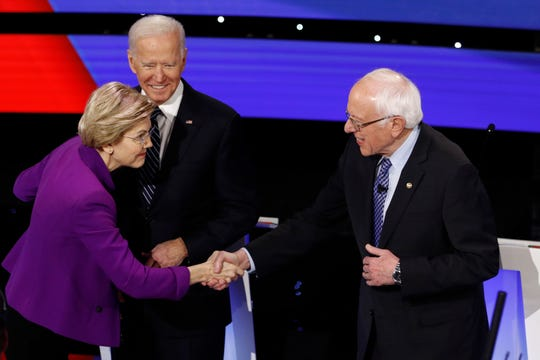 Democratic presidential candidates Sen. Elizabeth Warren, D-Mass., left, and Sen. Bernie Sanders, I-Vt., right greet each other as former Vice President Joe Biden, watches Tuesday, Jan. 14, 2020, before a Democratic presidential primary debate hosted by CNN and the Des Moines Register in Des Moines, Iowa.