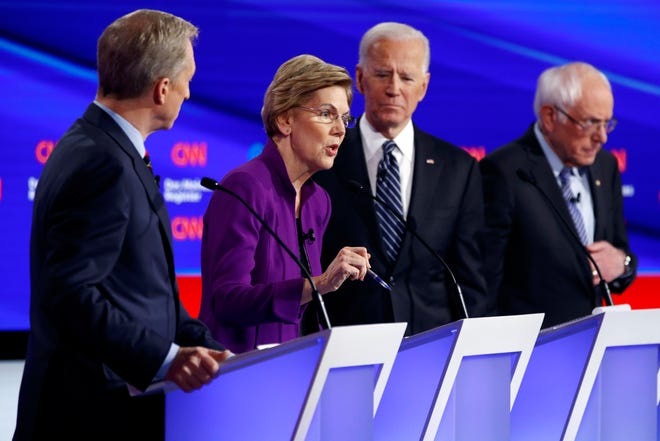 Democratic presidential candidate Sen. Elizabeth Warren, D-Mass., second from left, speaks as fellow candidates businessman Tom Steyer, left, former Vice President Joe Biden and Sen. Bernie Sanders, I-Vt., right, listen, Tuesday, Jan. 14, 2020, during a Democratic presidential primary debate hosted by CNN and the Des Moines Register in Des Moines, Iowa.