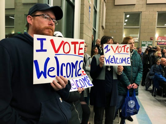 In this Dec. 9. 2019, file photo, residents in support of continued refugee resettlement hold signs at a meeting in Bismarck, N.D.