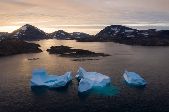 Large icebergs float away as the sun rises near Kulusuk, Greenland on Aug. 16, 2019.