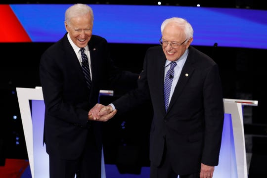 Democratic presidential candidates former Vice President Joe Biden, left, and Sen. Bernie Sanders, I-Vt., greet each other Tuesday, Jan. 14, 2020, before a Democratic presidential primary debate hosted by CNN and the Des Moines Register in Des Moines, Iowa.