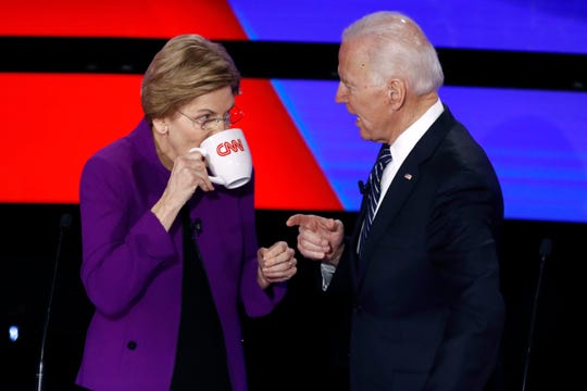 Democratic presidential candidates Sen. Elizabeth Warren, D-Mass., left, and former Vice President Joe Biden talk during a break, Tuesday, Jan. 14, 2020, in a Democratic presidential primary debate hosted by CNN and the Des Moines Register in Des Moines, Iowa.
