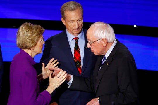 Democratic presidential candidate Sen. Elizabeth Warren, D-Mass., left and Sen. Bernie Sanders, I-Vt., talk Tuesday, Jan. 14, 2020, after a Democratic presidential primary debate hosted by CNN and the Des Moines Register in Des Moines, Iowa. Candidate businessman Tom Steyer looks on.
