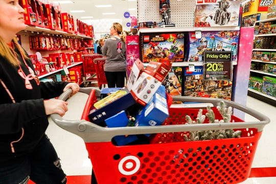 Shoppers browse the aisles during a Black Friday sale at a Target store in Newport, Ky. Comparable stores sales at Target fell well below the previous year, joining a growing list of retailers reporting a meager performances during the critical holiday shopping season.