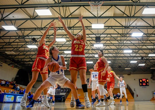 Memorial's Lydia Bordfeld (44) looks to shoot under defensive pressure from Mater Dei's Emily Beckerle (10) and Addy Nosko (25) as the Mater Dei Wildcats play the Memorial Tigers in the first round of the girls Southern Indiana Athletic Conference tournament at Memorial Tuesday, January 14, 2020.