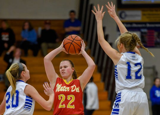 Mater Dei's Caitlyn Madden (22) is fights defensive pressure from Memorial's Ryeligh Anslinger (20) and Peyton Murphy (12) as the Mater Dei Wildcats play the Memorial Tigers in the first round of the girls Southern Indiana Athletic Conference tournament at Memorial Tuesday, January 14, 2020.