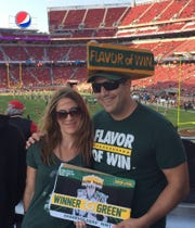 Wisconsin native and Packers fan Neal Dubisky and his wife Chelsea get in a plug for his Winner Green Bay gum at Levi's Stadium in Santa Clara, California.