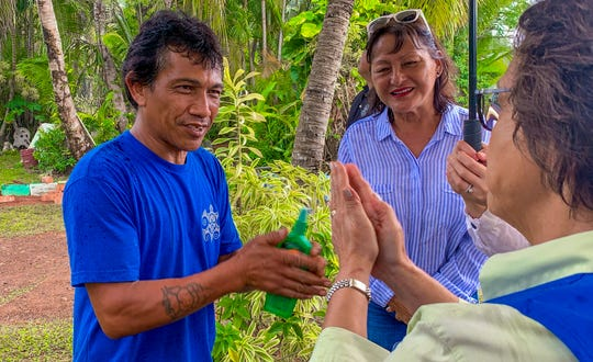 Dededo resident, John Mesa, left, gets advice on how to properly apply insect repellent from Gov. Lou Leon Guerrero, after receiving a bottle of repellent outside his home along Swamp Road on Wednesday, Jan. 15, 2020. Five thousand pump spray bottles of the repellent was donated by the CDC Foundation and shipped to Guam by SC Johnson to help residents protect themselves from the recent outbreak of the dengue virus, according to the Department of Public Health and Social Services.