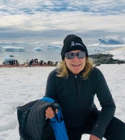 Terri Jump poses in front of penguins on her December trip to Antarctica.