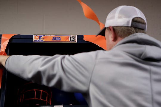 UTM head coach Brian Dunn adjusts decorations on Jada Watson's new locker in the Skyhawk women's locker room.