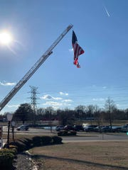 A giant American flag hangs over the Jackson Fairgrounds during the 2019 Guns & Hoses event.