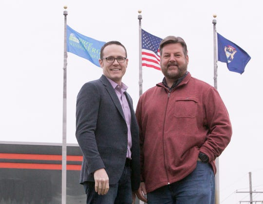 Adrian Beaver, left, and Matt Masters stand in front of the former Harley Davison showroom in Brighton Wednesday, Jan. 15, 2020, where they will relocate their business Pure Energy Window Company.