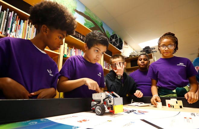 Robotics lab students Tabari Mays, 11, from left, Aiden Bosanto, 11, Lavin, 12, Jeremiah Coleman, 11, and M'Kaila Hill, 12, demonstrate the skills test navigated by their robot 'Kermit' for the LEGO robotics team, one of eight that have qualified for regionals from Barret's Chapel in Arlington on Wednesday, Jan. 15, 2020.