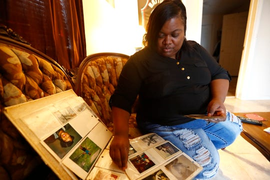 Tamara Hendrix, looks through a family photo album in her North Memphis home, where she grew up and has recently returned to live. Hendrix, who was formerly homeless, now works with the group Homeless Organizing for Power & Equality, a project of the Mid-South Peace and Justice Center.
