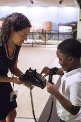 NCRM's educator Dory Lerner teaching a child how to use a dial phone