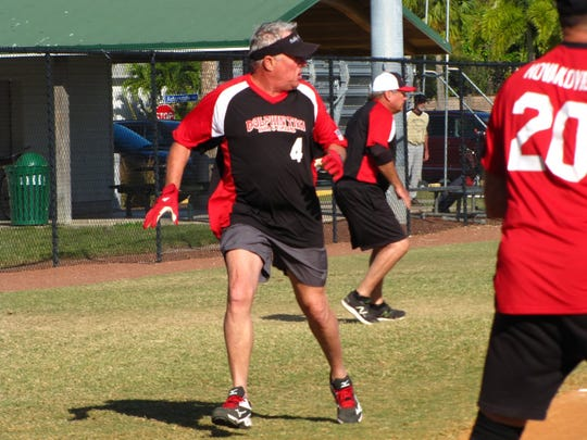 Bob Williams of the Dolphin Tiki scores a run as the Brewery's catcher Bill Novakovich covers home plate.