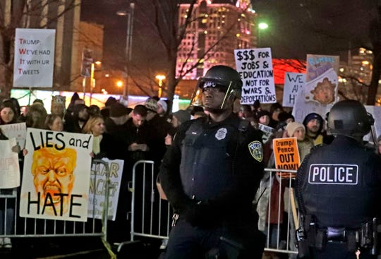 Police officers dressed in riot gear keep an eye on demonstrators and Trump fans in the overflow area as both sides yelled at each other while leaving the UW-Milwaukee Panther Arena following President Trump's rally Tuesday.